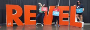 Three runners posing with the REVEL sign